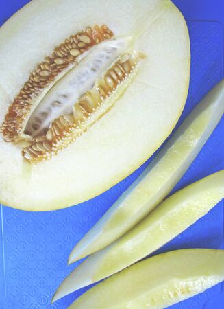 Ripe juicy melon on a blue cutting board. Melon cut into pieces, the seeds are inside. Top view. Vertical. 写真素材