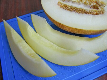 Ripe juicy melon on a blue cutting board. Melon cut into pieces, the seeds are inside. Top view.