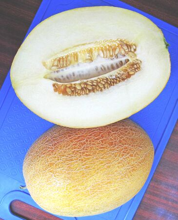 Ripe juicy melon on a blue cutting board. Melon cut in half, the seeds are inside. Top view. Vertical. 写真素材