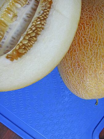 Ripe juicy melon on a blue cutting board. Melon cut in half, the seeds are inside. Top view. Vertical. Copy space.