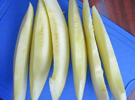 Sliced ripe melon on a blue cutting board. Top down view. 写真素材