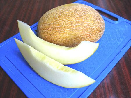 Ripe juicy melon on a blue cutting board. Slides from melon, top view.