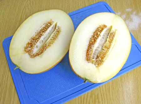 Ripe juicy melon on a blue cutting board. Melon cut in half, the seeds are inside. Top view. 写真素材