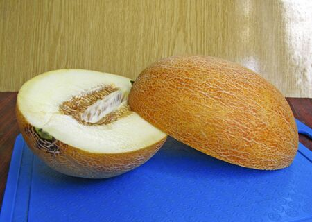 Ripe juicy melon on a blue cutting board. Melon cut in half, the seeds are inside. 写真素材