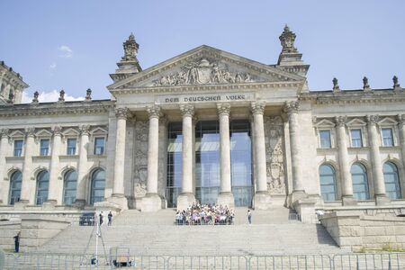 Berlin, Germany - 4th June, 2019: Reichstag building is the Bundestag Parliament. German parliament with group of tourists near it. The inscription on the facade: For the German people.