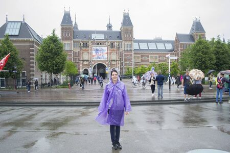 Amsterdam, Netherlands - 5th June, 2019: A young woman in a purple raincoat looks at the camera and smiles while standing against the background of the Reichsmuseum in Amsterdam. Rainy spring weather.