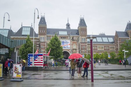 Amsterdam, Netherlands - 5th June, 2019: Dutch national museum. View of the square in front of the entrance to the Reichsmuseum in Amsterdam. People stand under an umbrella, cloudy weather.