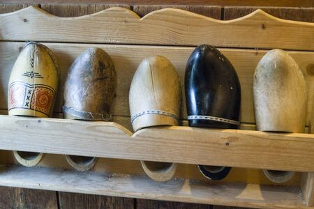 Zaanse Schans, Netherlands - 5th June, 2019: Traditional Dutch hand made wooden farmers shoes. An exhibition of five different damaged klompen on a wall shelf at the entrance to the Clog Museum.