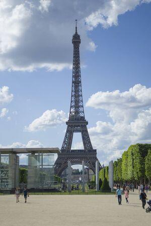 Paris, Frankreich, 6. Juni 2019: Blick auf den Eiffelturm von weitem. Touristen gehen um die Sehenswürdigkeiten herum. Vertikal. Editorial