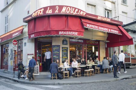 Paris, France - 6th June, 2019: Cafe with a red canopy on the corner of one of the old streets in the Montmartre district. People are sitting at the tables of a typical French cafe.