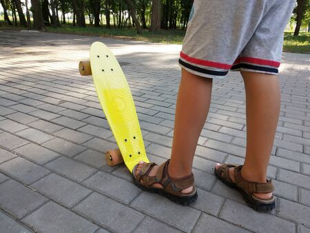 Feet of a little boy in a brown sandals on a yellow children's skateboard in the park. Close view. Summer activity concept.
