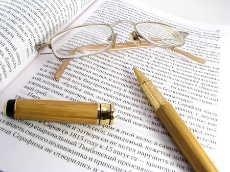 prochtennaja the opened book, glasses and the writing handle.