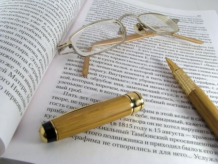 prochtennaja the opened book, glasses and the writing handle photo