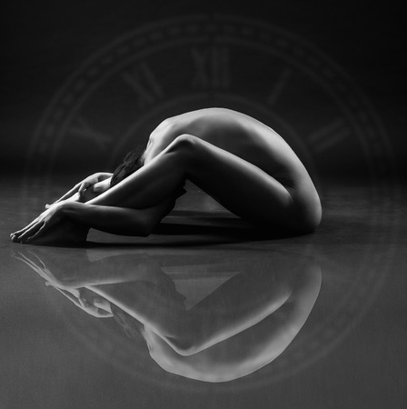 nude yoga: Flexibility and beauty. Beautiful sexy body of young woman on black background. Low key black and white studio photography. Conceptual posture. Amazing yoga poses with reflections