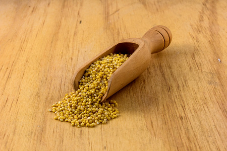 hulled: Hulled millet in wooden spoon Stock Photo