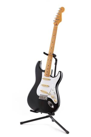 A vintage black and white electric guitar on a stand isolated on white Stock Photo