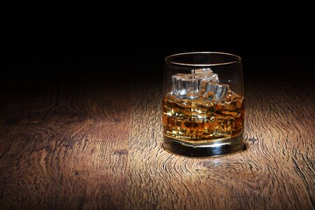 A Scotch in glass tumbler with ice rocks on old wood surface 스톡 콘텐츠