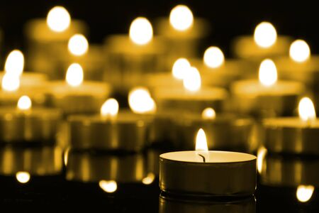 Candles on christmas night signifying hope. Gold. Background.With selective focus.
