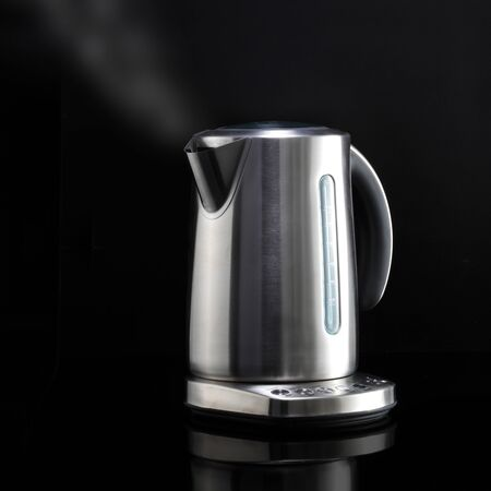 A modern kettle with steam on black reflective surface