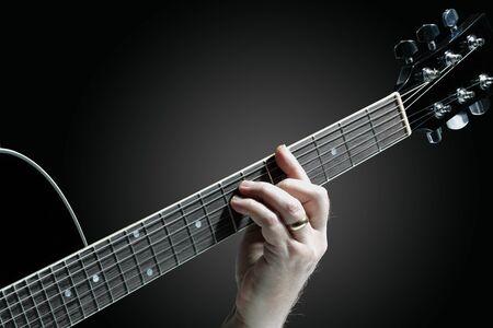 A Musician playing guitar on a dark graduated background 版權商用圖片