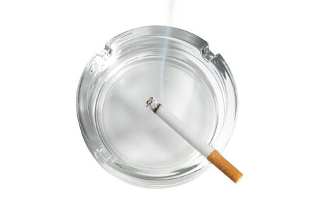 Top view of a cigarette lit in glass ashtray on white