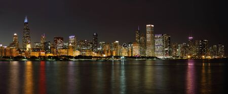 The Chicago skyline and waterfront at night with illuminated buildings reflected in the water of Lake Michigan