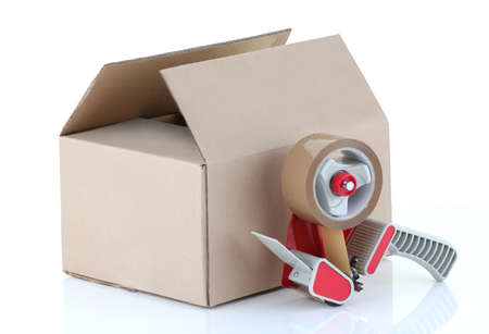 Cardboard box and packing tape gun on white