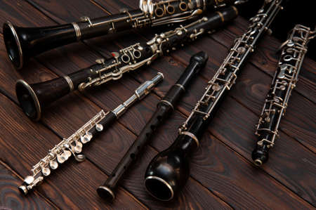 Woodwind instruments lie on a wooden surface. View from above