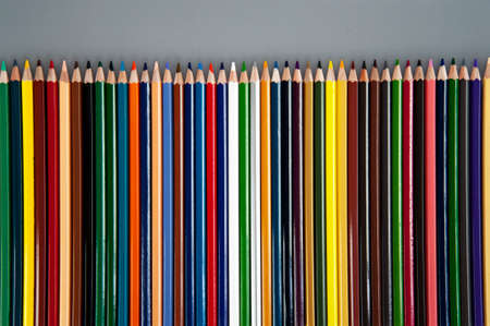 Multicolored pencils on gray background