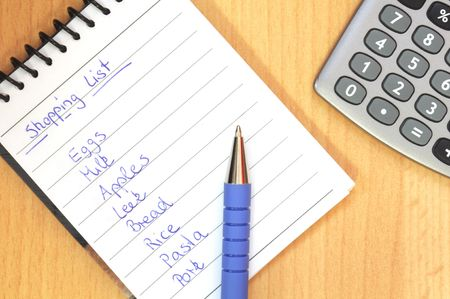 shopping list with pen and calculator on brown desk Stock Photo - 6698980