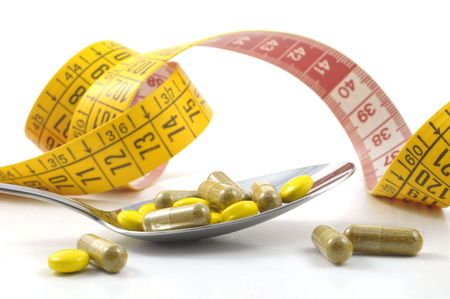 overbalance: measuring tape with tablets and spoon - diet concept Stock Photo