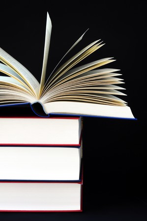 high stack of books on black background photo