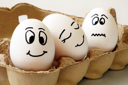 painted eggs: white eggs with different faces in a packet Stock Photo