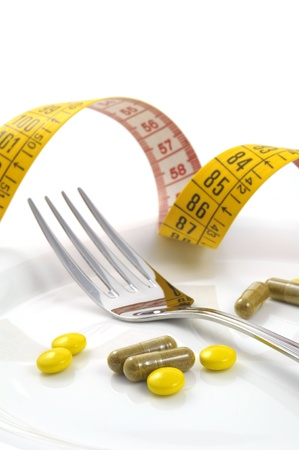 overbalance: measuring tape with tablets and fork - diet concept
