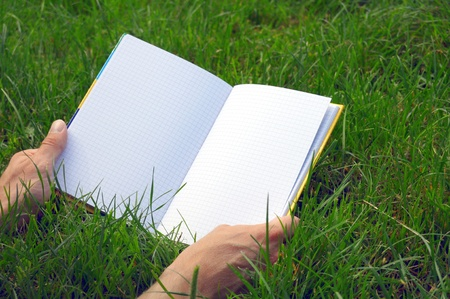 A blank opened book outdoors lying on the green grass. photo