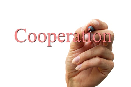 hand writing the word cooperation isolated on a white backgound Stock Photo - 8825795
