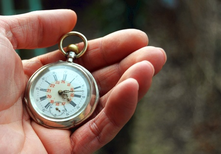 human hand holding a old pocket watch  Stock Photo