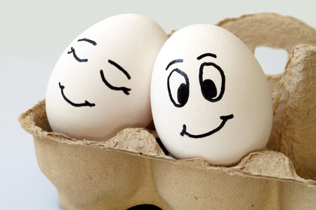 white eggs with different faces in a packet Standard-Bild