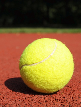 yellow tennis ball on the tennis court photo
