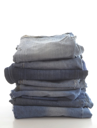 legs folded: stack of blue jeans, isolated on white background Stock Photo