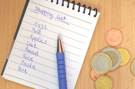 shopping list with pen and money on brown desk photo
