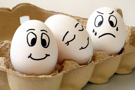 egg box: white eggs with different faces in a packet Stock Photo