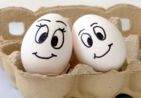 white eggs with different faces in a packet Stock Photo