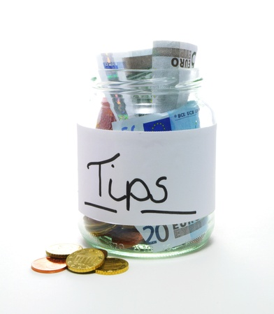 tip jar with bills and coins on white background Foto de archivo