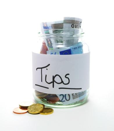 tip jar with bills and coins on white background Standard-Bild