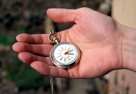 grandfather clock: human hand holding a old pocket watch  Stock Photo