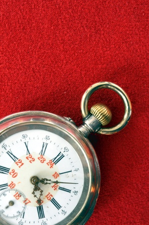 old pocket watch isolated on red background photo