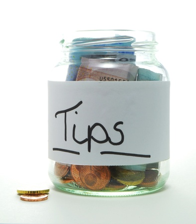 tip jar with bills and coins on white background Stock Photo - 11148319