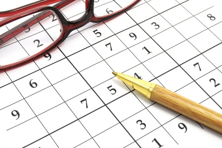 pen and glasses on an unfinished sudoku game photo