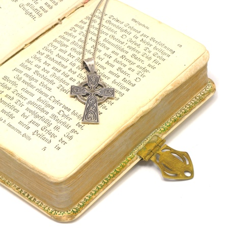 silver cross on bible isolated on white background photo